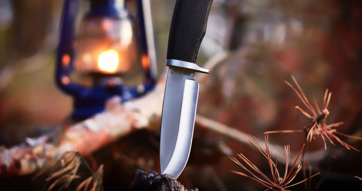 Knife digging into a log