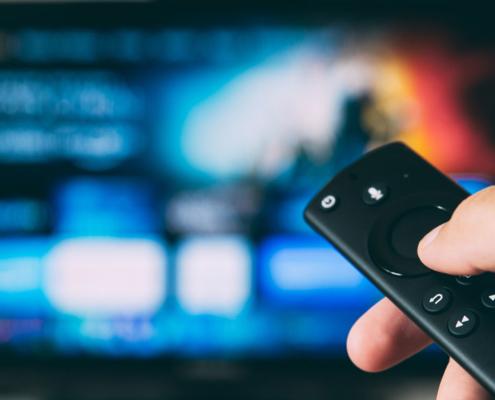 Person holding a TV remote