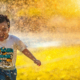 Child running through sprinklers