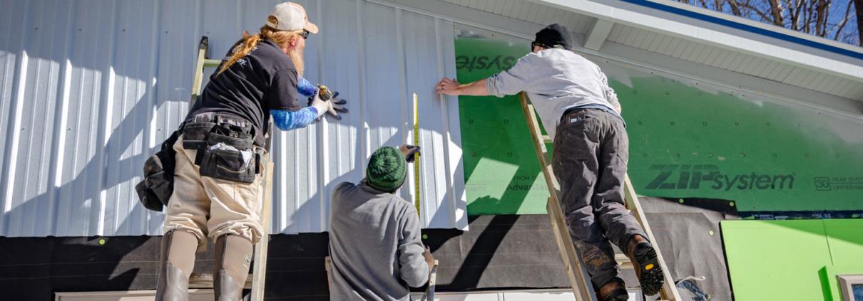 Contractors install siding